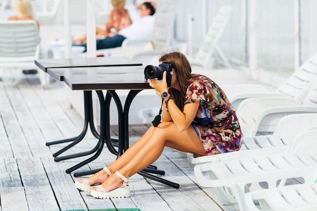 若い女の子がデジタル カメラで写真を撮っています。写真家はサンベッドに座っています