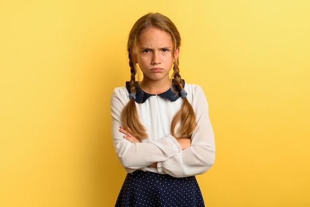 어린 소녀는 노란색에 뭔가에 대해 불행하고 화가납니다. 프리미엄 사진