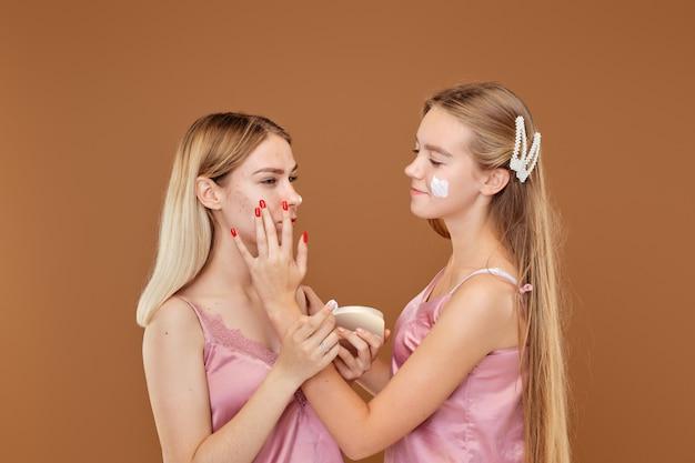 若い女の子はにきびに腹を立てており、友達は落ち着いて彼女をサポートしています