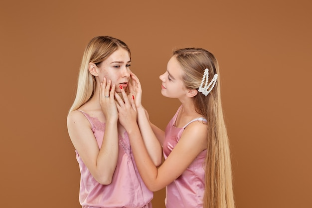 Young girl is upset about her acne and her friend calms and supports her
