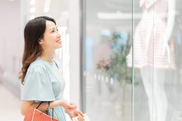 若い女の子は店の外で服を見ています