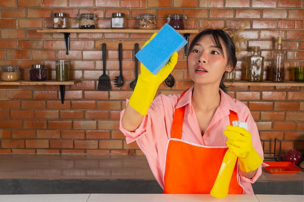 Young girl is wearing yellow gloves while cleaning the kichen room with duster in her house.