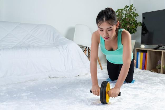 若い女の子が自宅でワークアウトしている、彼女は自宅でヨガを練習しています。ウイルスから健康的な生活の概念。