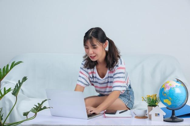 Молодая девушка работает во время использования labptop на диване у себя дома