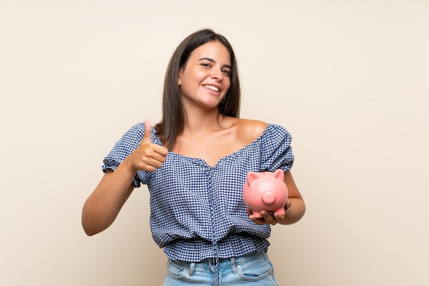 Young girl over isolated wall holding a big piggybank
