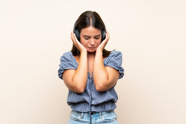Young girl over isolated wall listening to music with headphones