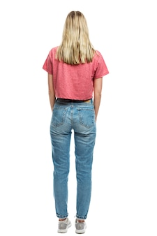 A young girl in jeans and a red t-shirt is standing. back view. full height. isolated on a white wall. vertical.