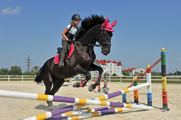 Young girl jockey riding a horse jumping over a barrier on equestrian competitions