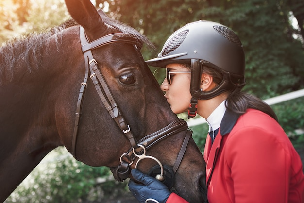 A young girl jockey talking and kissing her horse. she loves the animals and joyfully spends her time in their environment.