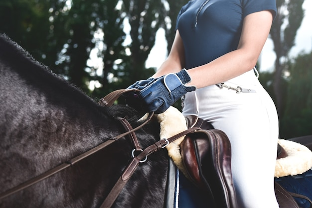 Молодая девушка-жокей тренирует лошадь к скачкам летом. фото крупным планом