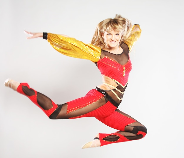 若い女の子が体操ダンスでジャンプ