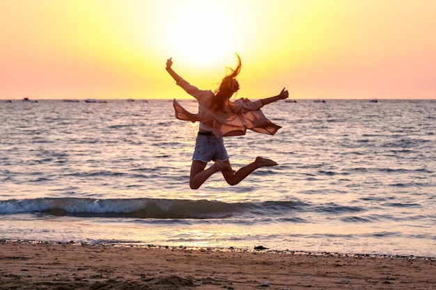 Young girl jumping on the beach at summer sunset.