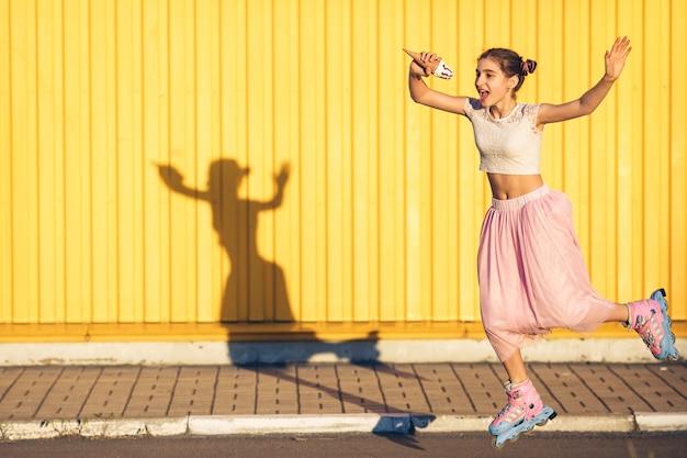 롤러 스케이트에 점프하고 노란색 벽에 아이스크림을 먹는 어린 소녀