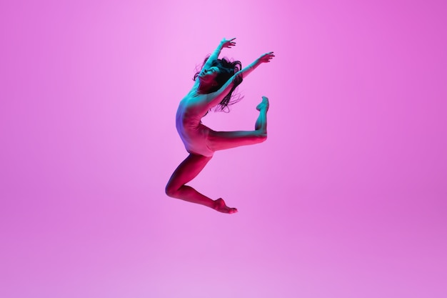 Young girl jumping on pink wall