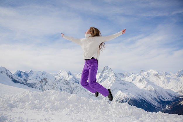 Young girl jumping in a sky slope