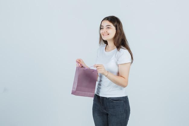 Tシャツ、ジーンズで紙袋を保持し、陽気に見える若い女の子、正面図。