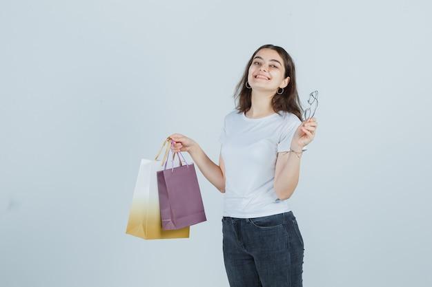 Молодая девушка держит подарочные пакеты и очки в футболке, джинсах и выглядит счастливой. передний план.
