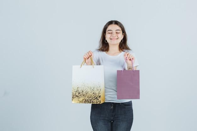 Молодая девушка держит подарочные пакеты в футболке, джинсах и выглядит довольным, вид спереди.