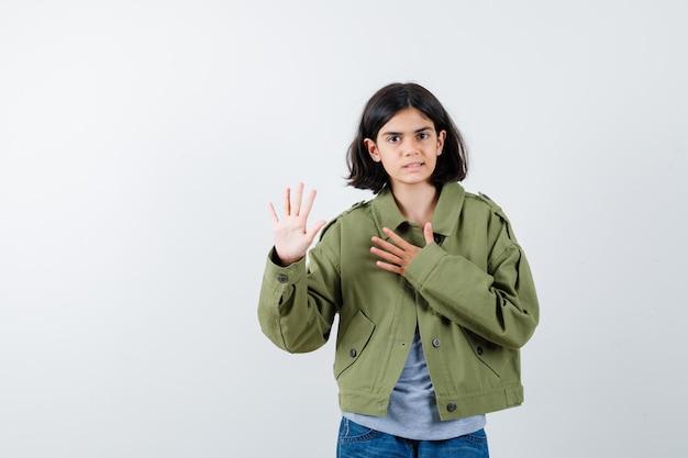 Молодая девушка держит руку на груди и дает обещание или клятву в сером свитере, куртке цвета хаки, джинсовых брюках и серьезно выглядит, вид спереди.