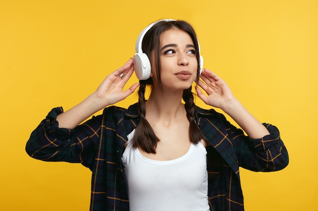 어린 소녀 헤드폰에 손을 유지 노란색 벽 위에 음악을 듣는