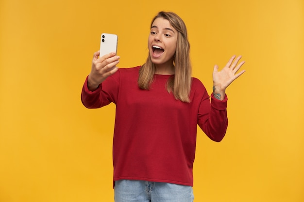 Young girl keeps mobile phone in her hand, looking on it like making selfie or a video call, opened her mouth like saying something