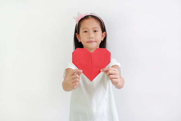 Young girl kid show red heart sign against white background. focus at red heart paper