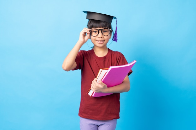 Young girl kid student touching glasses and wearing degree hat and holding books
