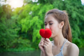 Young girl kissing red heart. Model woman with red heart. Female kiss love symbol.