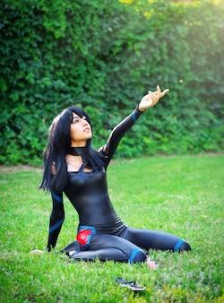 Молодая девушка становится на колени и протягивает руку к небу. оригинальный косплей персонажа