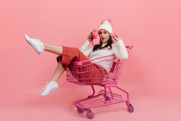 Young girl in knitted clothes poses with pink camera while sitting in supermarket trolley on isolated wall.