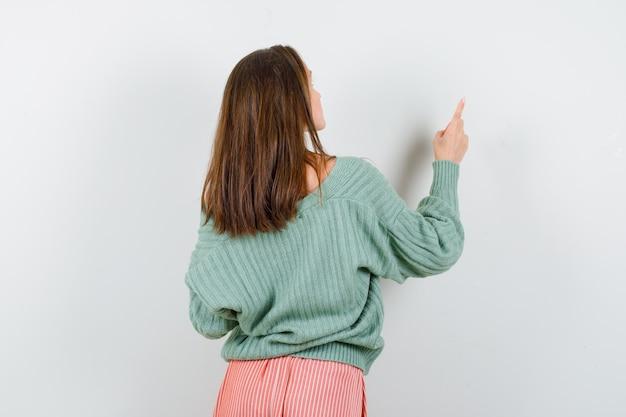 Giovane ragazza in maglieria, gonna girando indietro, indicando il muro con il dito indice e guardando seducente, vista frontale.