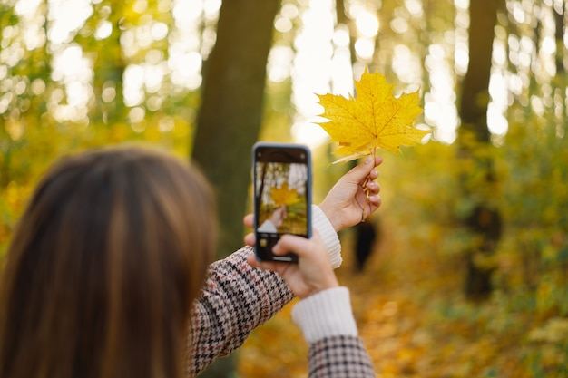 Young girl laughs and photographs autumn leaves on the phone the concept of lifestyle mobility