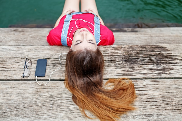 A young girl lays on a pier and listens to music on headphones.