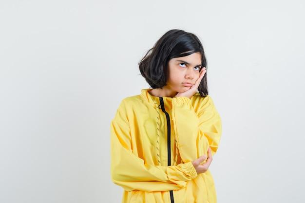 손바닥에 뺨을 기울고 노란색 폭격기 재킷에 뭔가에 대해 생각하고 잠겨있는 찾고 어린 소녀.