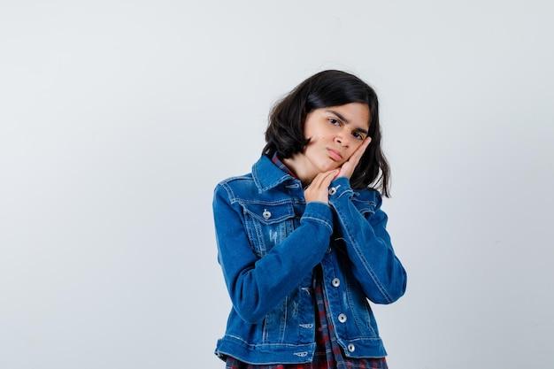 어린 소녀는 체크 셔츠와 진 재킷을 입고 손바닥에 뺨을 기대고 진지한 전면 모습을 보고 있습니다.