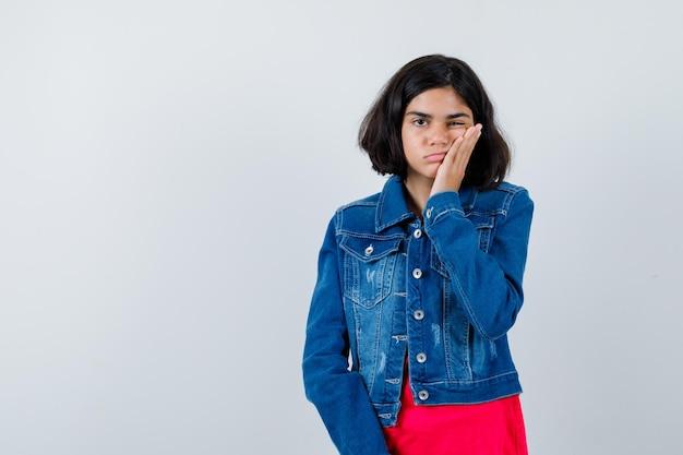 赤いtシャツとジージャンで手のひらに頬をもたれ、疲れているように見える若い女の子