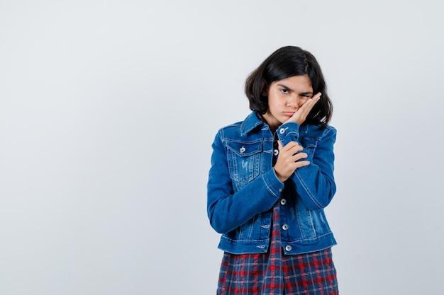 어린 소녀는 손바닥에 뺨을 기대고 체크 셔츠와 진 재킷에 대해 생각하고 잠겨있는 찾고 있습니다. 전면보기.