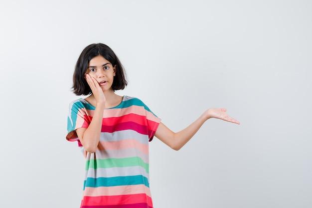 カラフルなストライプのtシャツで何かを保持し、驚いて、正面図を見て、右に手を伸ばしながら手のひらに頬を傾けている若い女の子。
