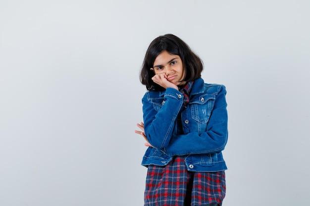 Giovane ragazza che si appoggia guancia sul palmo in camicia a quadri e giacca di jeans e sembra carina. vista frontale.