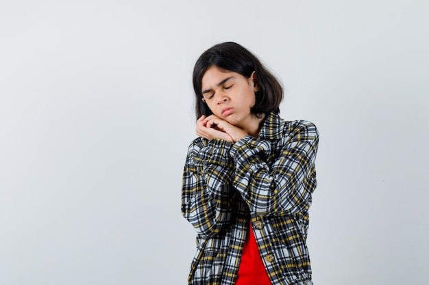 Giovane ragazza che si appoggia guancia sul palmo in camicia a quadri e t-shirt rossa e sembra assonnata, vista frontale.
