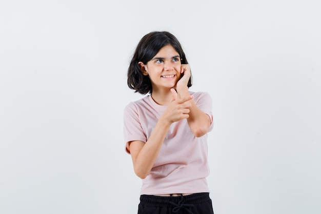 Young girl leaning cheek on palm in pink t-shirt and black pants and looking happy