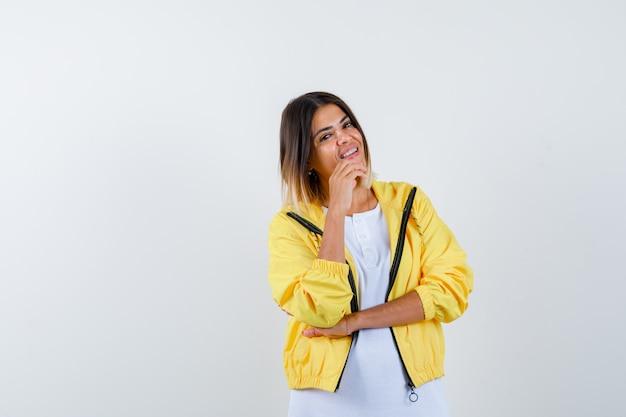 Ragazza giovane con il mento pendente a portata di mano in t-shirt bianca, giacca gialla e aspetto allegro. vista frontale.