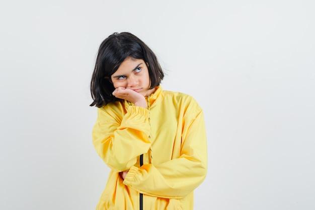 손바닥에 턱을 기울고 노란색 폭격기 재킷에 뭔가에 대해 생각하고 잠겨있는 찾고 어린 소녀.