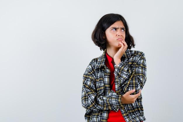 手のひらに顎をもたれ、肘に手を置き、チェックのシャツと赤いtシャツで目をそらし、怒っている少女。正面図。