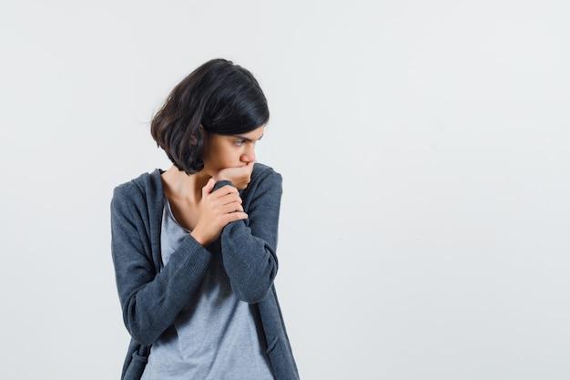 어린 소녀는 손바닥에 턱을 기울이고 밝은 회색 티셔츠와 어두운 회색 지퍼 앞 까마귀에 대해 생각하고 잠겨있는 찾고 있습니다.
