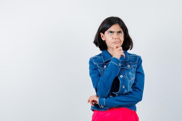 あごを手のひらに寄りかかって、赤いtシャツとジージャンで何かを考えて物思いにふける少女。正面図。