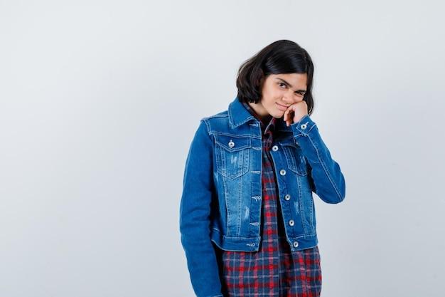 Giovane ragazza che si appoggia la mano sulla guancia in camicia a quadri e giacca di jeans e sembra carina, vista frontale.