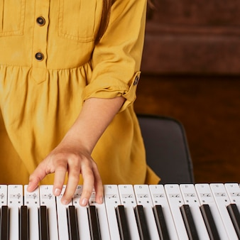 Young girl learning how to play electronic keyboard at home