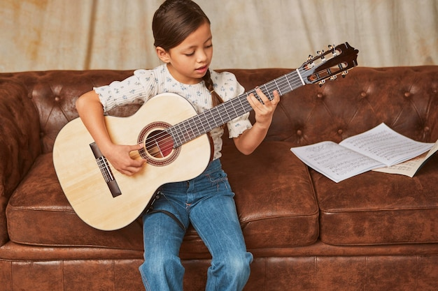 Young girl learning how to play guitar at home
