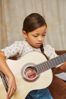 Ragazza che impara a suonare la chitarra a casa